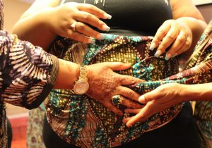 Women wrapping another woman's belly with African cloth