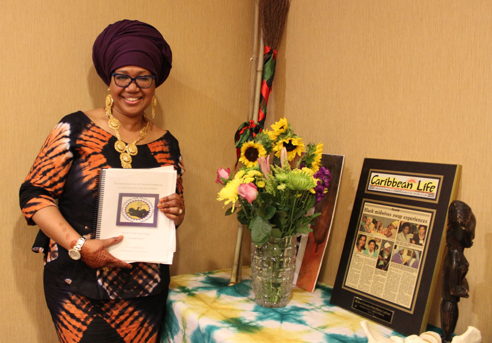 Shafia Monroe with Caribbean Life article, Full Circle Doula manual and flowers